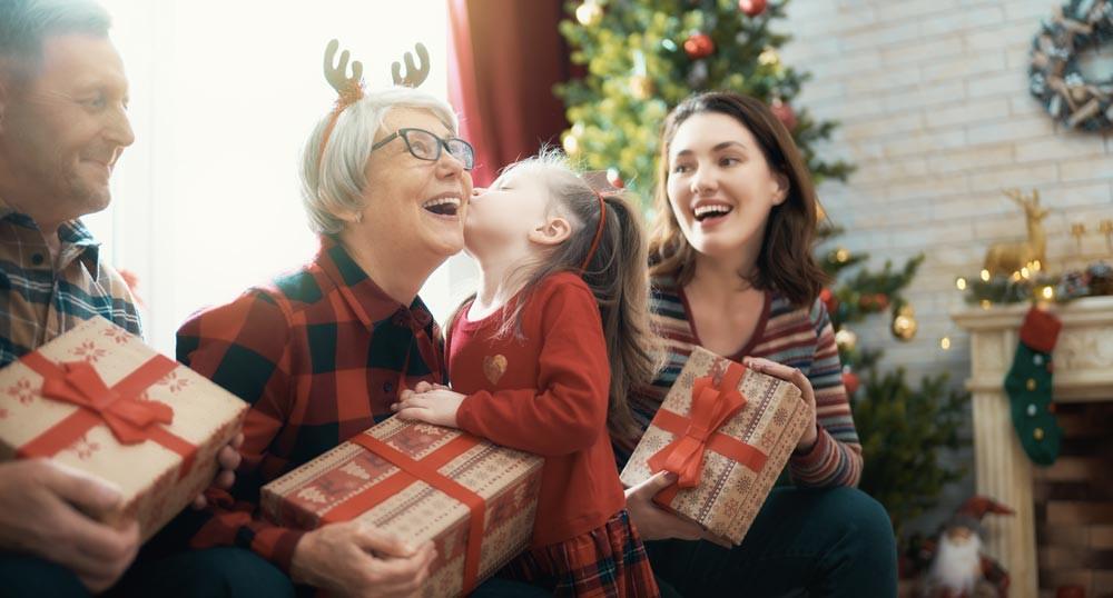 petite fille offrant un cadeau de noel à sa mamie