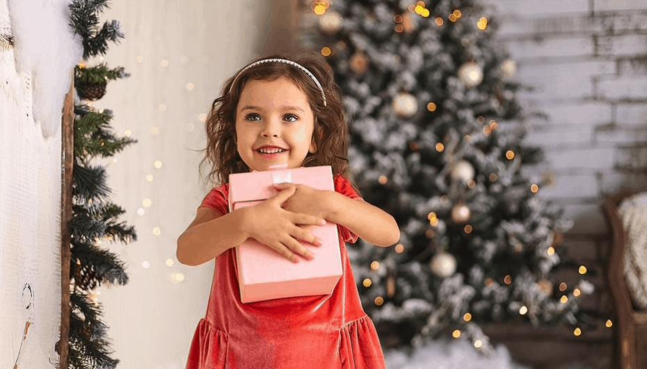 enfant tenant un cadeau de noel dans ses bras