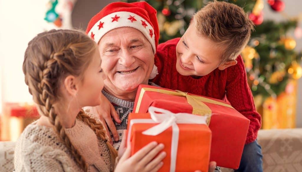jeunes enfants offrant un cadeau à leur grand père